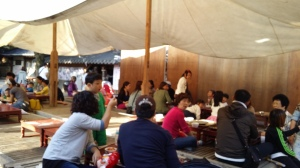 People sitting underneath a tent in the Folk Market Place.
