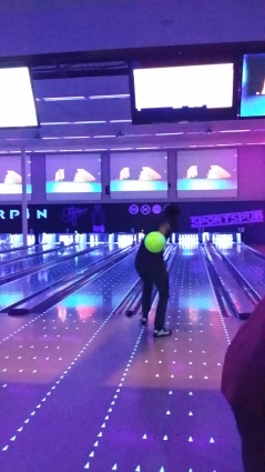 A friend of mine bowling with music videos playing above the pins.